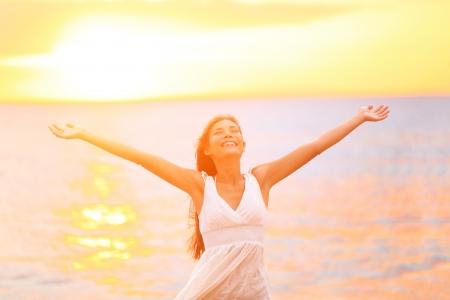 mujeres felices: Mujer de la libertad feliz y brazos abiertos libres en la playa al atardecer soleado. Alegre hermosa mujer euf�rica buscar sonriendo junto al mar durante las vacaciones de las vacaciones de verano. Pretty ni�a cauc�sica asi�ticos multirracial. Foto de archivo