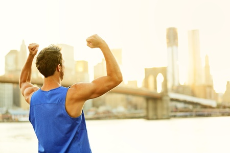 Winning cheering success fitness runner man in New York City celebrating happy and flexing strong muscles after running workout training outside with Brooklyn Bridge in background. photo
