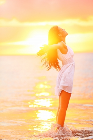 bliss: Free woman enjoying freedom feeling happy at beach at sunset. Beautiful serene relaxing woman in pure happiness and elated enjoyment with arms raised outstretched up. Asian Caucasian female model.