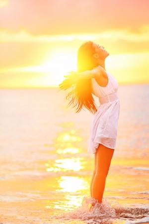 Mujer libre y liberado sentimiento de felicidad en la playa al atardecer. Hermosa mujer relajante serena en pura felicidad y el placer eufórico con los brazos levantados extendidos hacia arriba. Caucásica modelo femenino asiático.