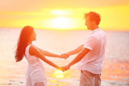 로맨틱 커플의 연인이 해변 일몰에 손을 잡고. 여름 여행 해변 휴가 동안 함께 낭만과 재미 사랑에 행복 다민족 젊은 부부. 아시아 여자 태양 백인 남자