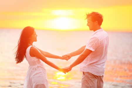 Romantic couple lovers holding hands at beach sunset. Happy multiethnic young couple in love having romance and fun together during summer travel beach vacation. Asian woman, Caucasian man in sun.