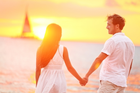 romantico: Pareja feliz en el amor al atardecer playa rom�ntica. La joven pareja interracial tomados de la mano con el romance y la diversi�n fuera caminando en la playa durante las vacaciones de verano viajar juntos. Disfrutando del sol Foto de archivo
