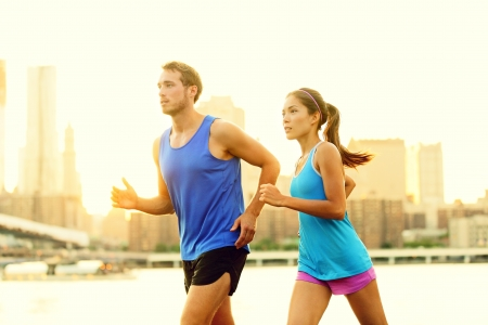 run out: City running couple jogging outside. Runners training outdoors working out in Brooklyn with Manhattan, New York City in the background. Fit multiracial fitness couple, Asian woman, Caucasian man. Stock Photo