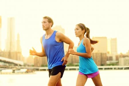 dentro fuera: Ciudad de pareja corriendo correr afuera. Formaci�n Corredores trabajan al aire libre en Brooklyn con Manhattan, Ciudad de Nueva York en el fondo. Montar pareja multirracial fitness, mujer asi�tica, hombre de raza cauc�sica.