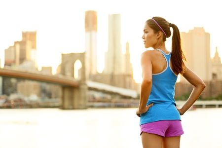 Fitness woman runner relaxing after city running and working out outdoors in New York City, USA. Girl looking and enjoying view of Brooklyn Bridge. Mixed race Asian Caucasian female model. Stock Photo