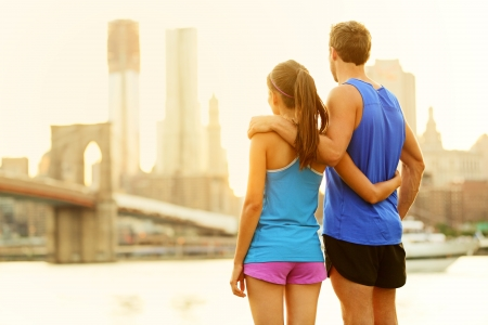girls night out: Fitness couple relaxing after running in Brooklyn, New York City, USA. Happy sporty fit young interracial couple enjoying view of Brooklyn Bridge after jogging training outside. Woman and man in 20s.