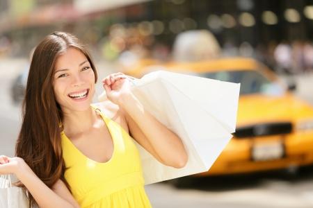 carro supermercado: Mujer con bolsas Feliz comprador compras, Ciudad de Nueva York, Manhattan, EE.UU.. Fresca hermosa modelo de mujer alegre caminando en la calle con vestido de verano con taxi amarillo en el fondo. Chica multirracial. Foto de archivo