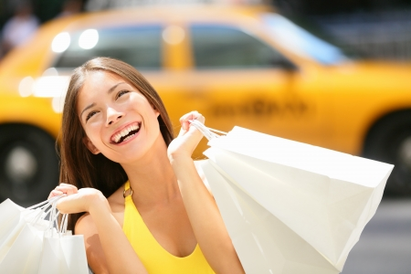 Shopper woman shopping in New York City, Manhattan, USA. Shopper girl holding shopping bags smiling happy with yellow taxi cab in background. Young multiracial Asian Caucasian female model in dress. Stock Photo - 19387059