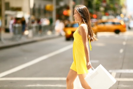 woman street: Shopping woman walking outside in New York City holding shopping bags. Shopper smiling happy crossing the street outdoors while on travel on Manhattan, United States. Beautiful model in summer dress. Stock Photo