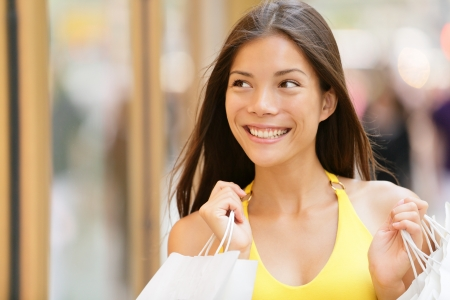 window display: Shopping woman looking at shop window display outside. Shopper girl smiling happy holding shopping bags looking at city store front. Pretty beautiful lovely multiracial Asian Caucasian female model. Stock Photo