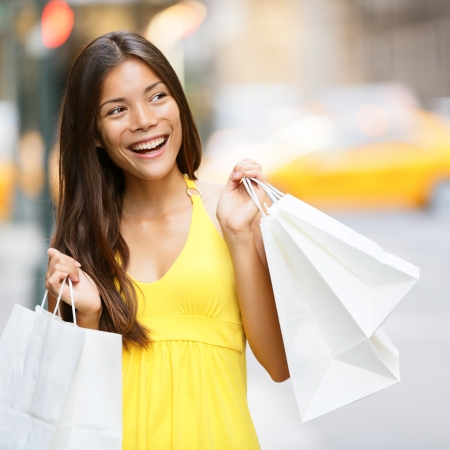 spree: Shopping woman in New York City, Manhattan, USA. Shopper holding shopping bags walking smiling happy during shopping spree in outside. Young multiracial Asian Caucasian female model in yellow dress.