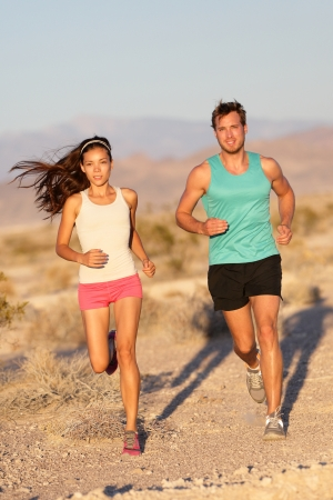 Asian woman runner and Caucasian male fitness sport model jogger training together for cross-country marathon photo
