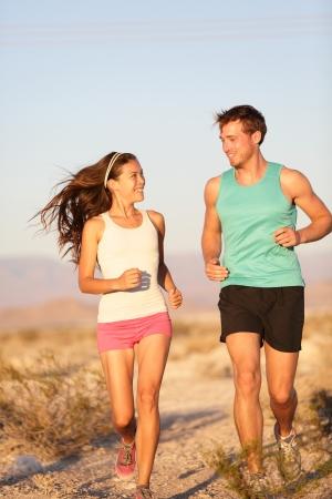 Glückliche Läufer Frau und Joggen Mann arbeitet lächelnd während Langlaufloipe run Standard-Bild