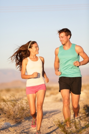 Happy runner woman and jogging man working out smiling during cross-country trail run photo