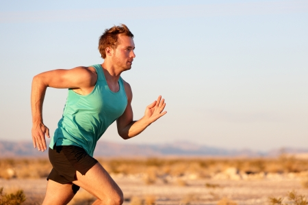 Running man sprinting cross country trail run. Male fit sport fitness model training for marathon outside in beautiful landscape. Caucasian handsome guy in his 20s. photo