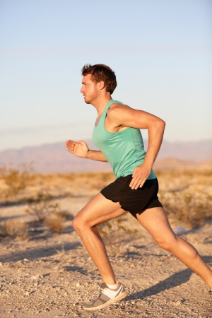 Male fitness sports model jogging exercising outside in summer sun photo