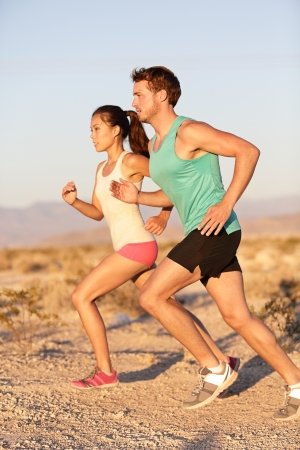Runner man and sport woman training and jogging outside in cross country run outside at summer sunset