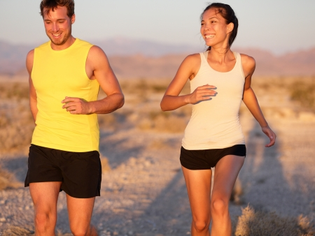 joggers: Fitness sport couple running jogging outside laughing happy training together outdoors Stock Photo