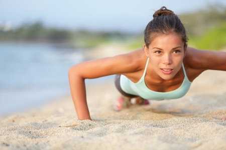 Push-ups fitness woman doing pushups outside on beach photo