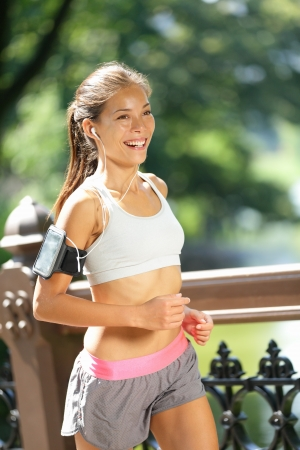woman jogging: Runner wearing earphones and armband for smart phone Stock Photo