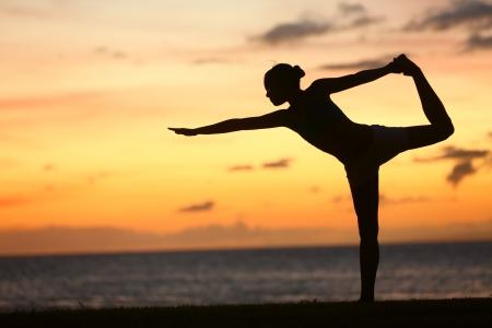 Mujer de la yoga en la puesta del sol serena en la playa haciendo una pose rey bailarín