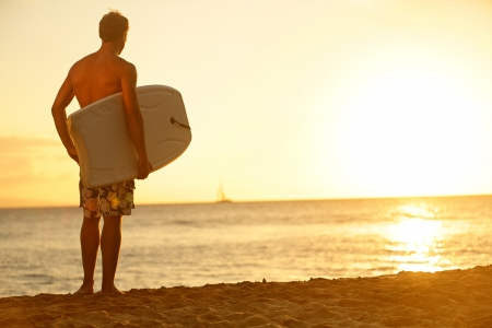 Fit male body surfer guy enjoying sunset and bodyboarding on summer holidays vacation on tropical beach photo