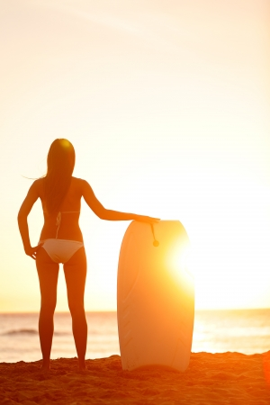 Summer surfer beach woman enjoying sunny sunset by the sea photo