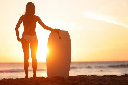 Surfing girl holding surfboard looking at ocean sea and sunshine photo