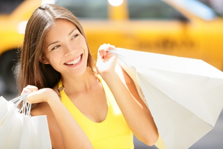 Beautiful happy summer shopper holding shopping bags walking outside smiling with yellow taxi cab in background