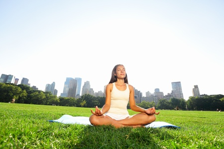Meditating woman in meditation in New York City Central Park in yoga pose photo
