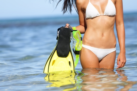 midsection: Travel beach fun concept - woman holding snorkeling fins standing in blue water under sunny sky on vacation holiday trip on tropical beach. Mid-section of bikini girl having summer fun.