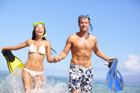 Beach couple having fun in water laughing with snorkeling fins together smiling happy and joyful photo