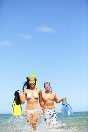 Happy couple having fun in ocean water on tropical beach with snorkeling fins equipment running laughing together photo