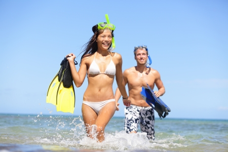 Happy couple beach summer vacation travel fun. Woman and man laughing with joy with snorkeling fins equipment on tropical beach under sunny blue sky. Multiracial couple, Asian woman, Caucasian man. photo