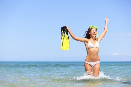 Cheering ecstatic girl running in water splashing holding fins during summer holiday vacation photo