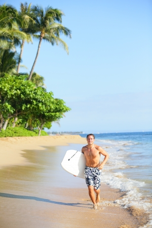 Beach lifestyle man surfer with surfing body board running in water on tropical beach photo