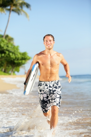man surfer with surfing body board running in water on\ tropical beach