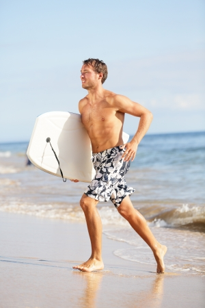 Beach water sports surfing man with body surfboard running\ happy during summer holiday