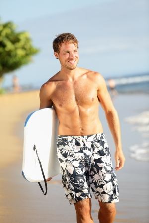 Man on beach holding body surfing body board doing water sports photo