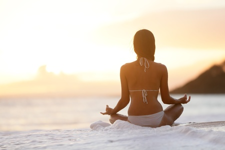 serenity: Meditation - Yoga woman meditating at serene beach sunset  Girl relaxing in lotus pose in calm zen moment in the ocean water during yoga holidays resort retreat  Multiracial girl  Stock Photo