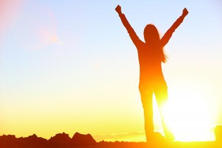 osiągnął: Szczęśliwa kobieta sukcesu obchodzi nagradzany na Åšwit stoi dumny z podniesionymi rÄ™kami do góry nad gÅ'owÄ… w obchodach, które osiÄ…gnęły szczyt Mountain Top cel podróży podczas pieszej wÄ™drówki