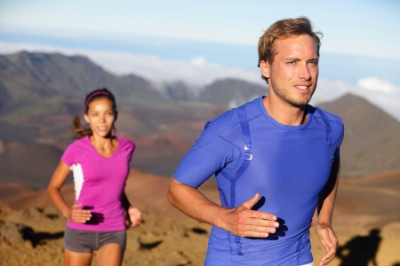 extreme terrain: Runners trail running athletes  Young fitness runner couple training trail running cross-country run for marathon  Fit man in compression t-shirt and woman model working out together  Multiracial  Stock Photo