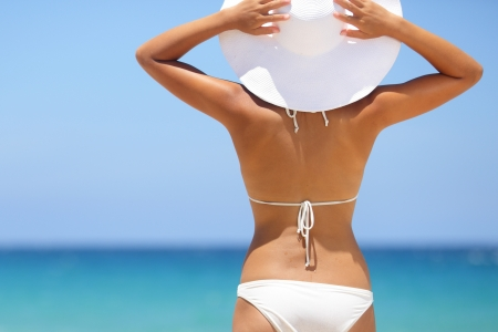 Travel woman on beach enjoying blue sea and sky wearing white beach sun hat and bikini. Beautiful pretty stylish young asian model from behind on vacation holidays. Stock Photo