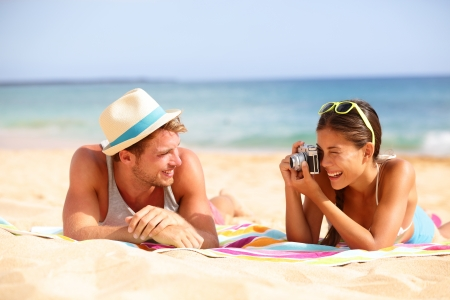 season photos: Beach fun couple travel. Woman taking photo picture of man smiling happy with retro vintage camera, Cool trendy modern hipster interracial couple on summer holidays vacation on tropical beach. Stock Photo