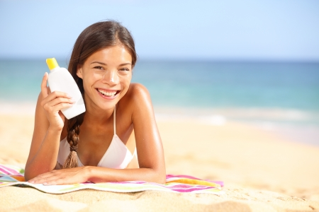 Sunscreen woman showing suntan lotion bottle. Beautiful smiling happy asian woman with suntan cream in plastic container lying on beach during summer travel vacation. Mixed race female model. photo