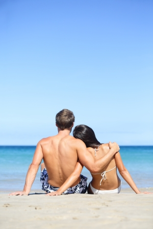 Beach lifestyle couple in love on vacation. Happy young interracial couple embracing and hugging enjoying ocean sea view and summer sun and blue sky during holidays travel. Asian woman, Caucasian man. photo