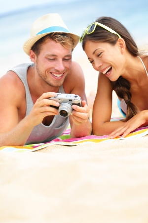Happy couple fun on beach laughing together looking at summer vacation travel photo pictures on retro vintage camera. Joyful interracial trendy modern hipster couple, Asian woman, Caucasian man. photo