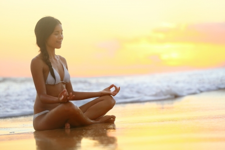 retreat: Relaxing and meditation - Yoga woman meditating at serene beach sunset. Girl relaxing in lotus pose in calm zen moment in the ocean water during yoga holidays resort retreat. Multiracial girl.
