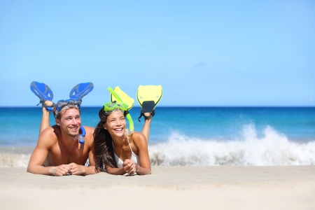 Beach travel couple having fun snorkeling. Happy young multiracial couple lying on summer beach sand with snorkel equipment looking to side at copy space after swimming with fins and mask on vacation. photo